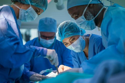 Healthcare workers performing surgery on patient in operating room. Team of surgeons are operating in emergency room. They are protective workwear in hospital.
